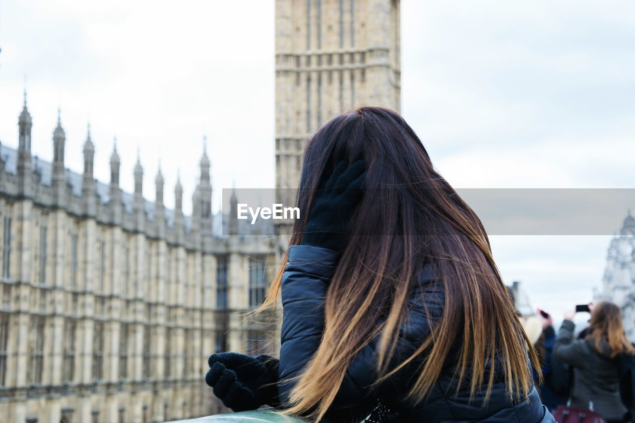 Rear view of woman looking at big ben against sky