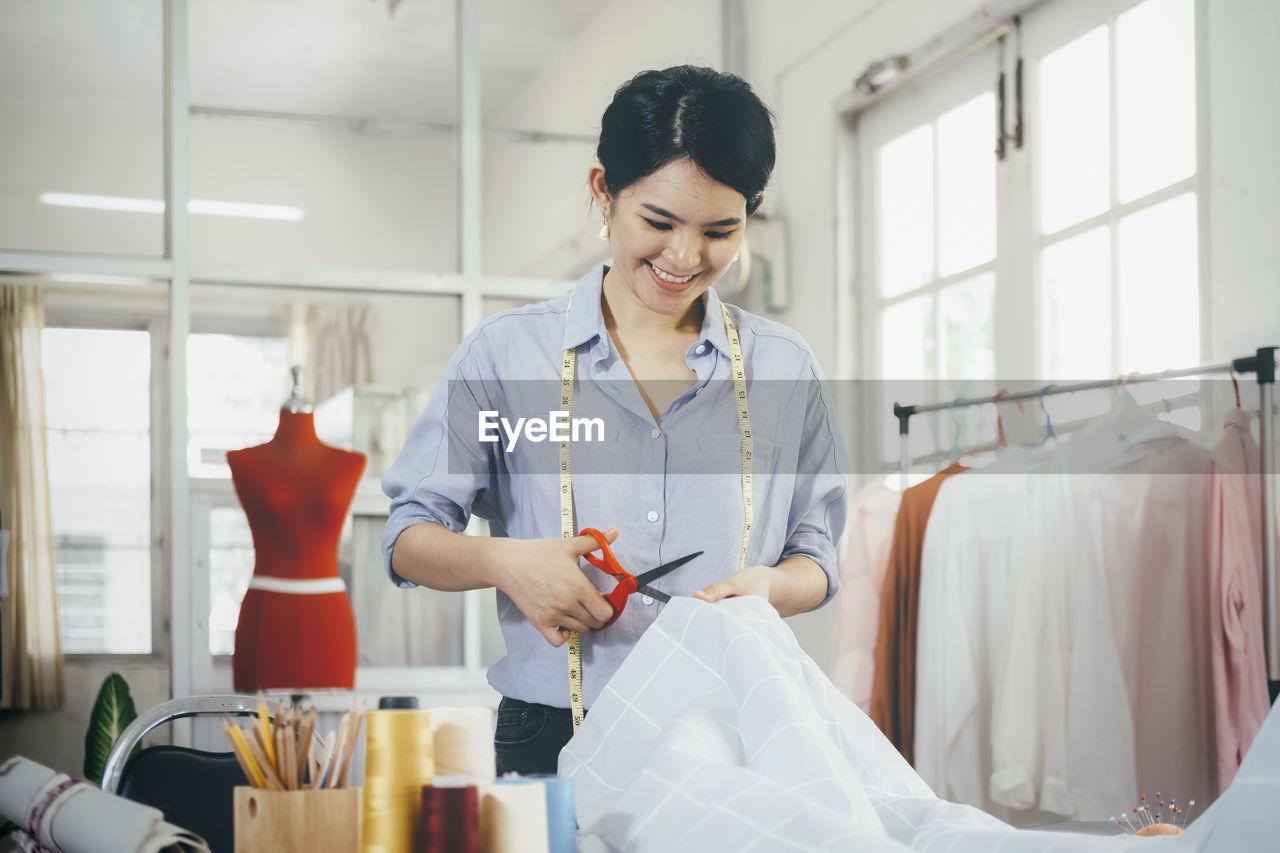 Smiling fashion designer cutting textile at boutique