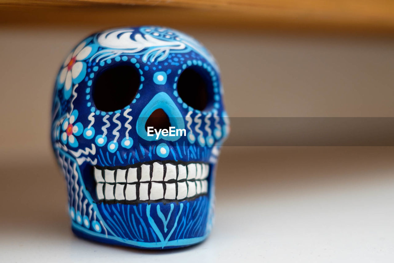CLOSE-UP OF HUMAN SKULL ON BLUE TABLE