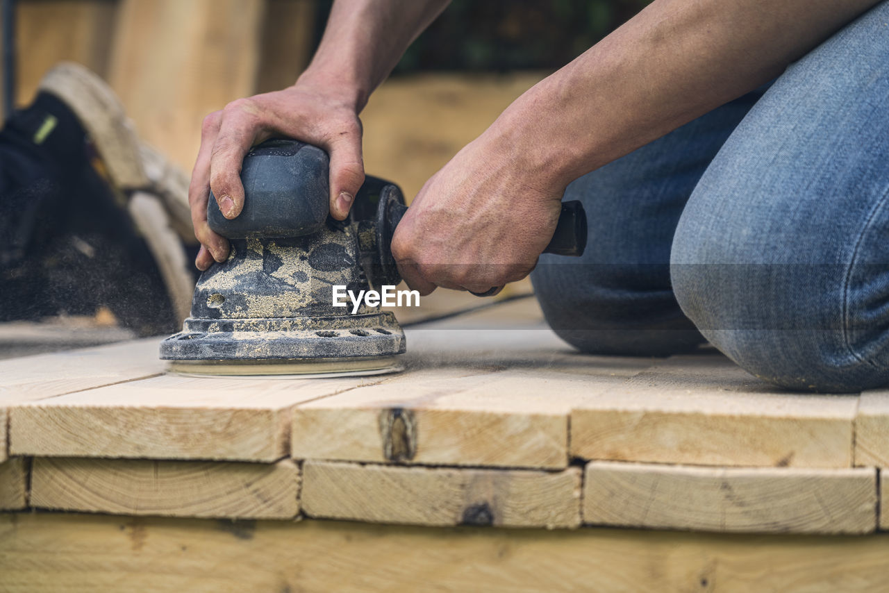 LOW SECTION OF MAN WORKING AT WOOD