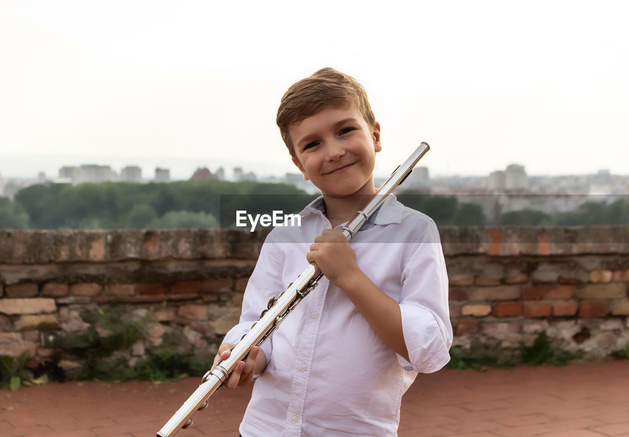 Portrait of cute little flautist outdoors.