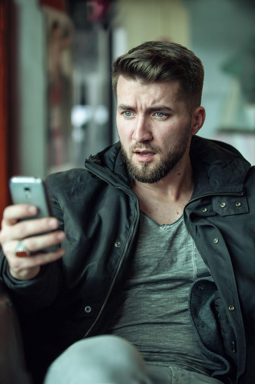 Portrait Of Surprised Man Using Mobile Phone
