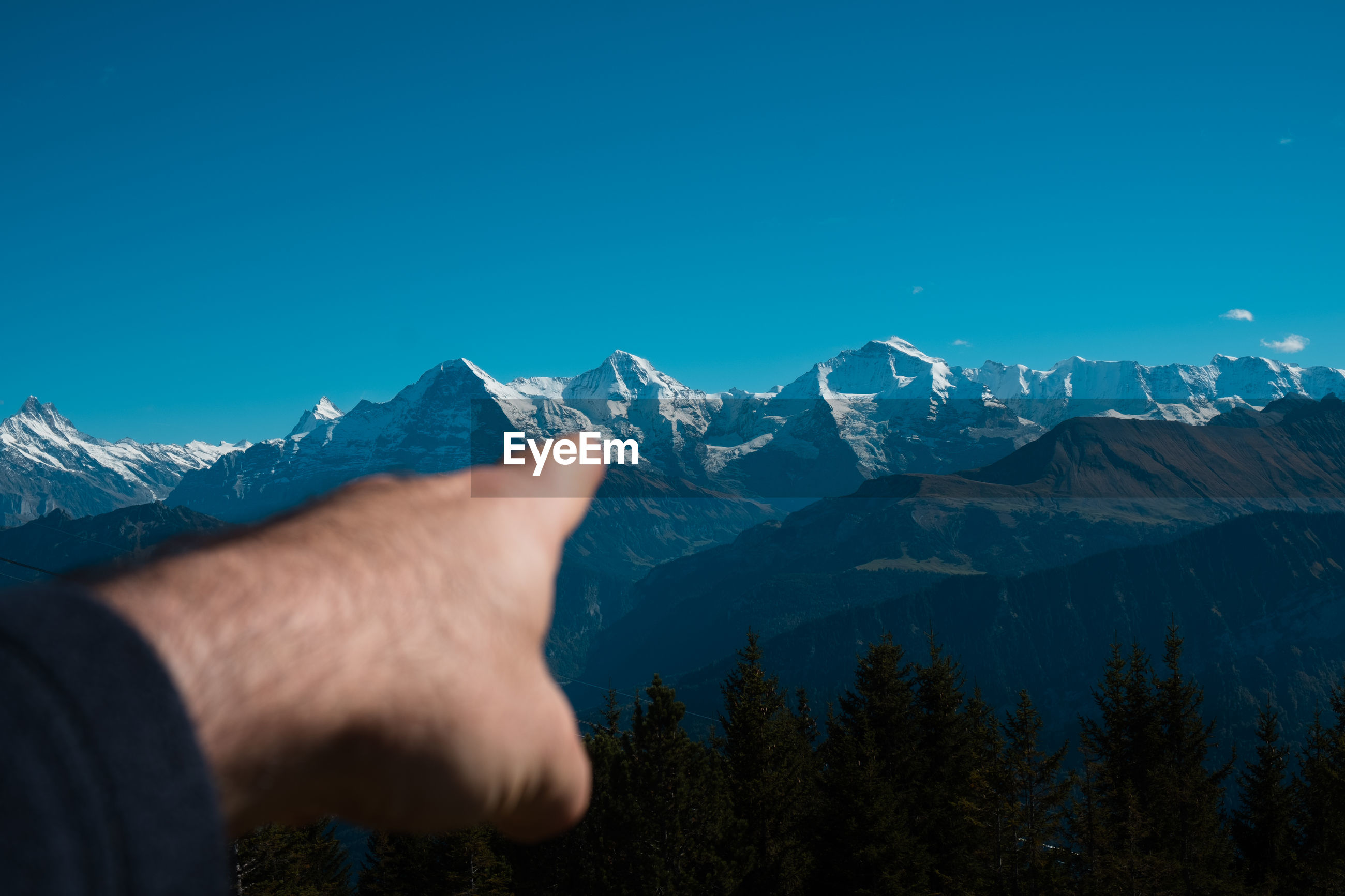Cropped hand of man pointing at snowcapped mountains