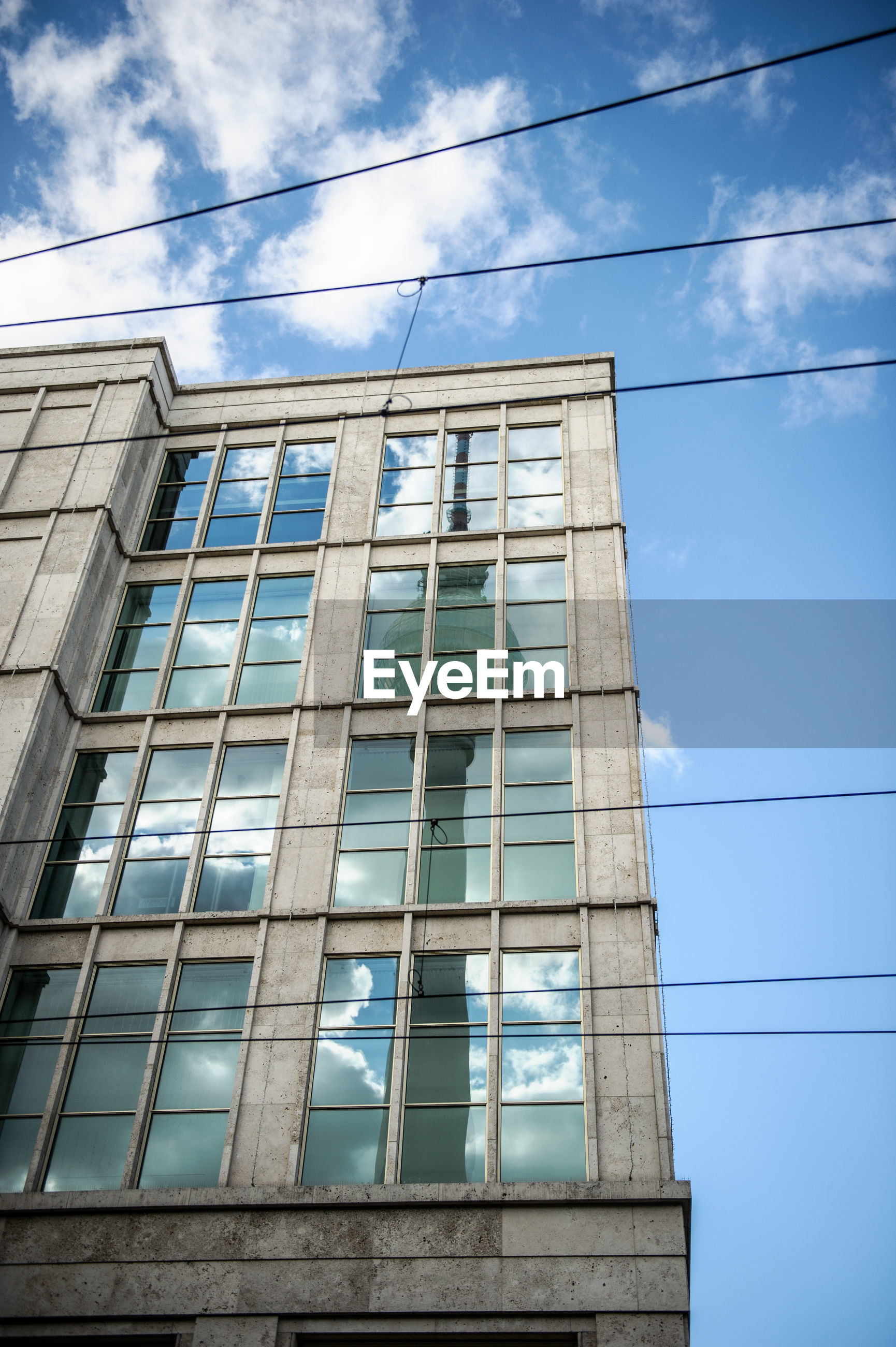 Low angle view of modern building with reflection of fernsehturm against blue sky