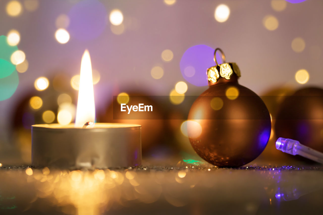 illuminated, celebration, close-up, indoors, candle, christmas, decoration, glowing, no people, burning, flame, holiday, christmas decoration, fire, selective focus, event, focus on foreground, fire - natural phenomenon, celebration event, christmas ornament, lens flare, purple, luminosity