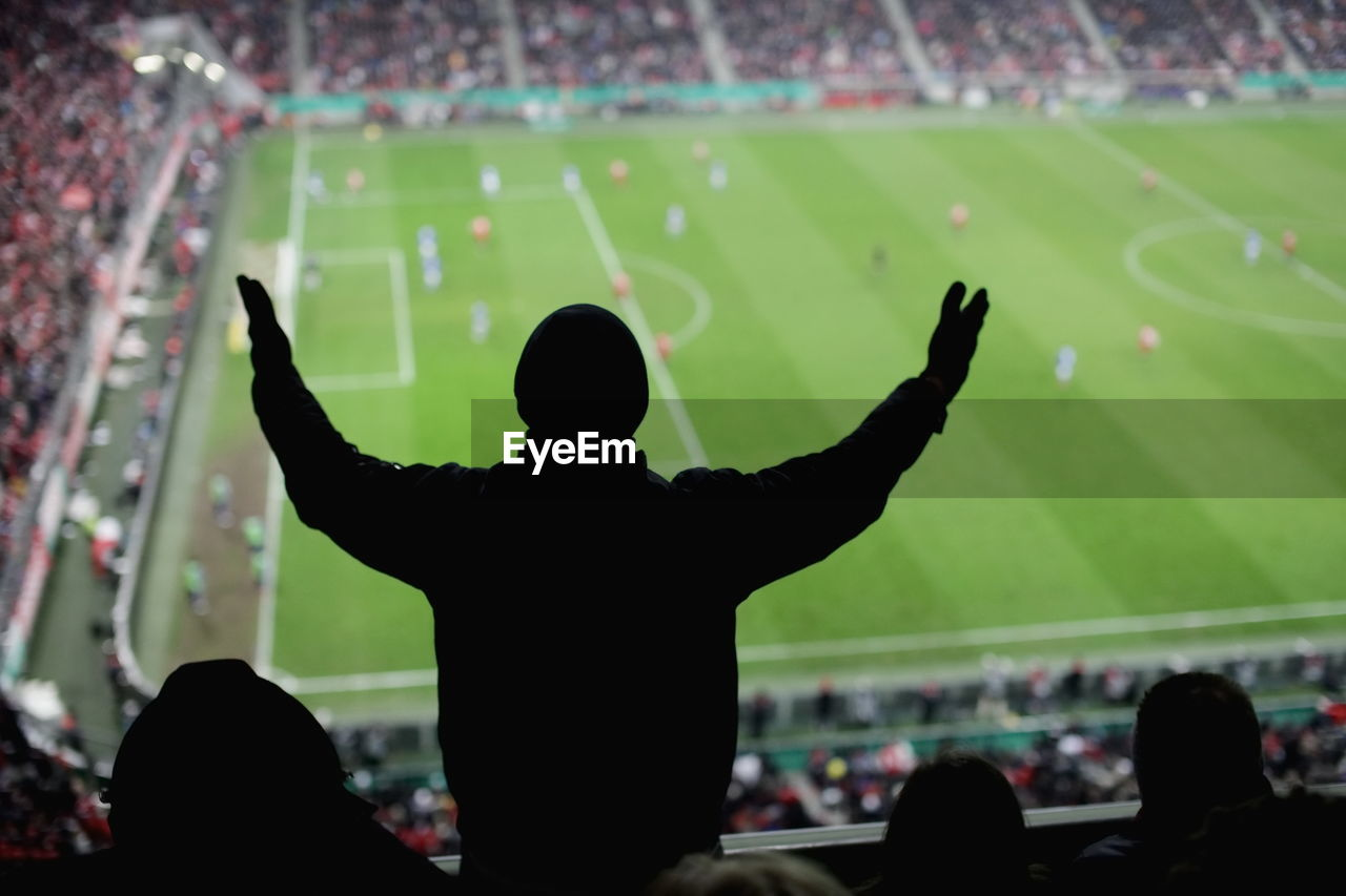 Rear View Of Spectator With Arms Outstretched Standing At Stadium During Soccer Match