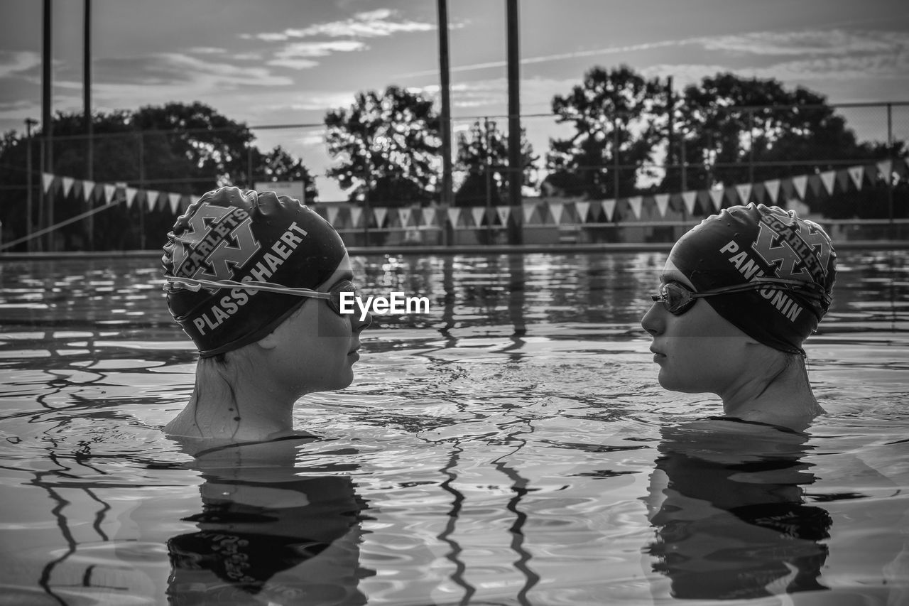 REAR VIEW OF PEOPLE AT SWIMMING POOL