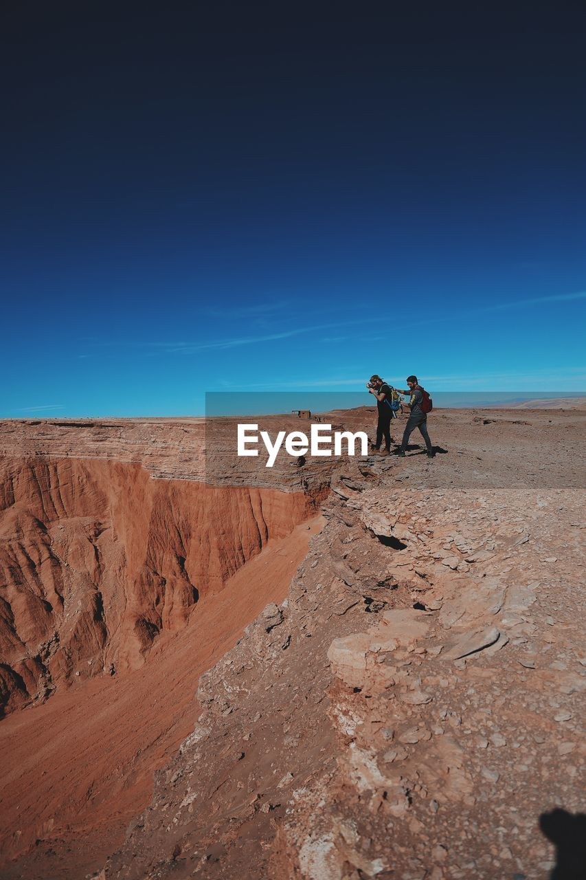Man Photographing Through Camera With Friend While Standing On Cliff Against Blue Sky