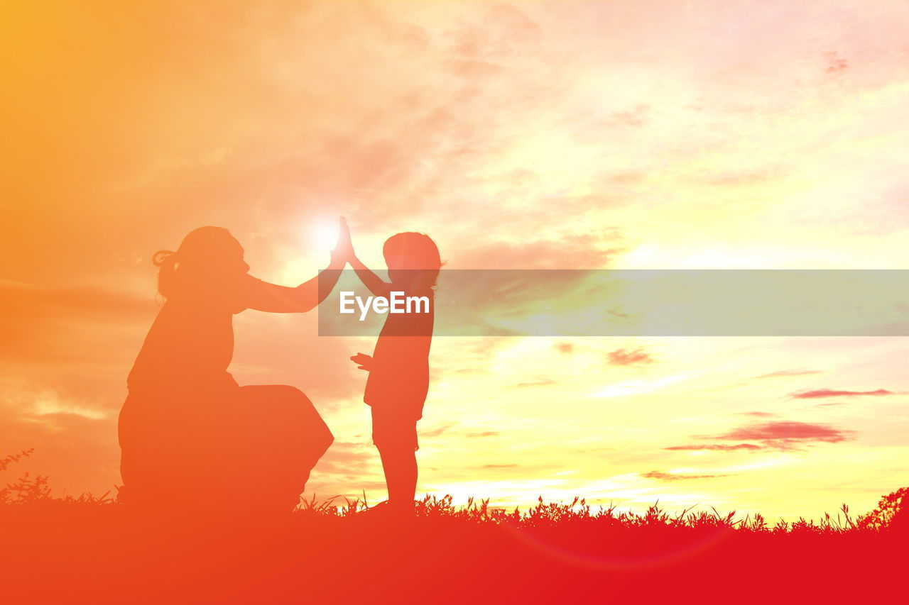 Silhouette mother giving high-five to daughter on field against sky during sunset