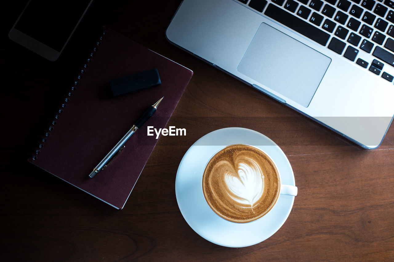 High angle view of coffee cup with diary and laptop on wooden table