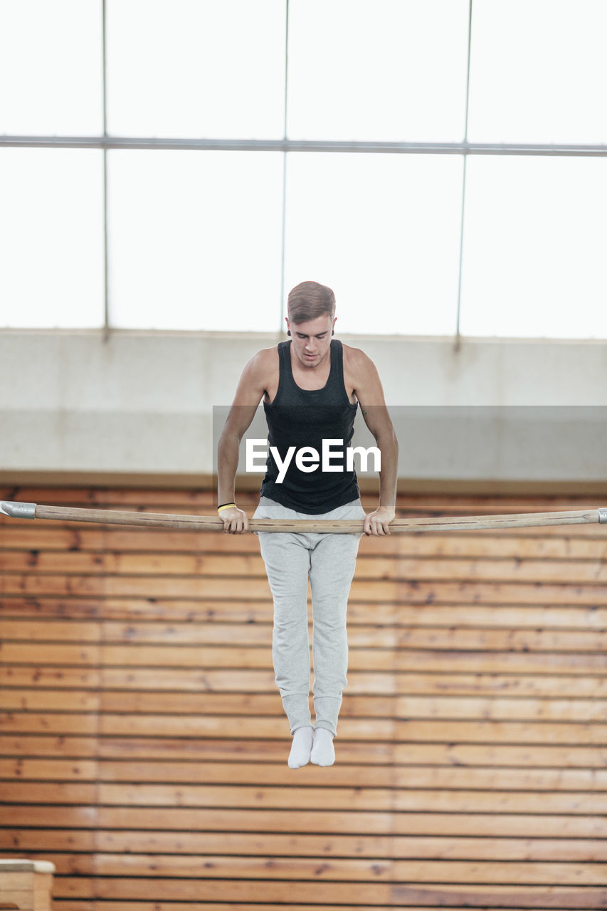 one person, sport, young adult, lifestyles, sports clothing, front view, healthy lifestyle, full length, architecture, exercising, real people, indoors, built structure, leisure activity, window, clothing, young men, casual clothing, effort, teenager