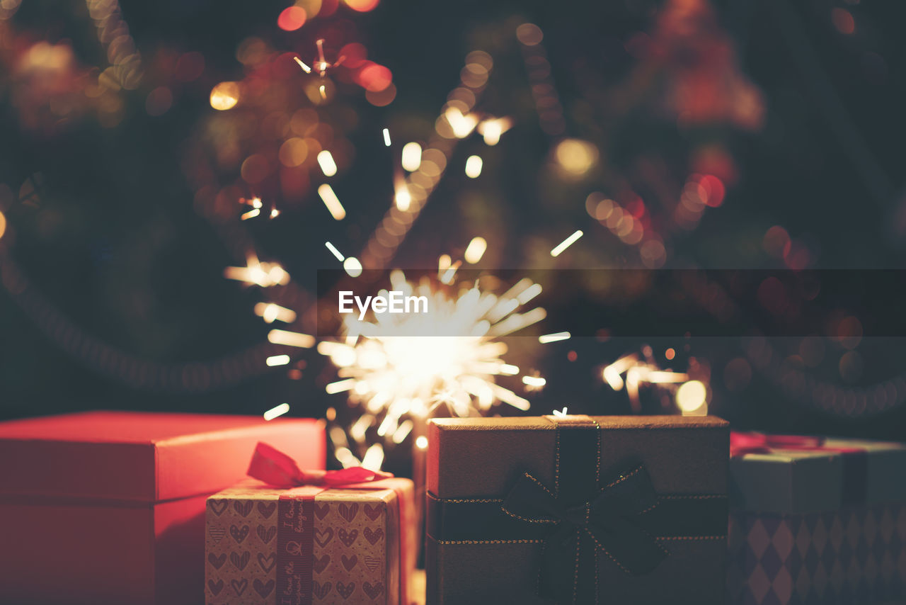 Close-up of sparklers and christmas gifts at night