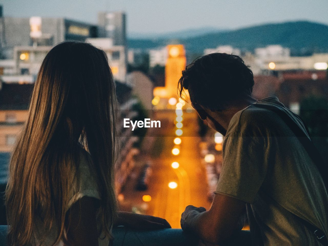 YOUNG COUPLE LOOKING AT VIEW FROM BALCONY