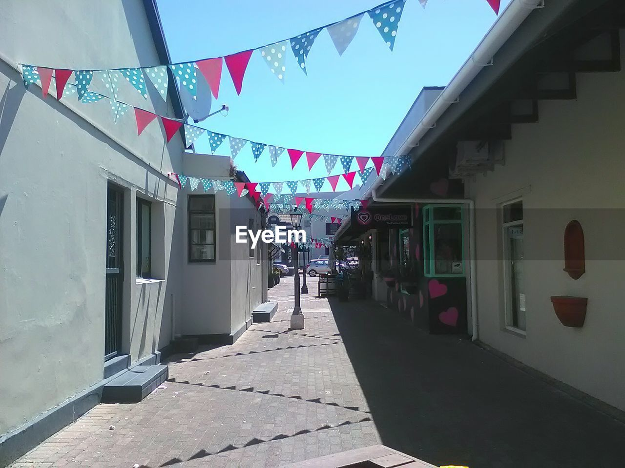 building exterior, bunting, architecture, built structure, celebration, outdoors, day, multi colored, sunlight, no people, sky