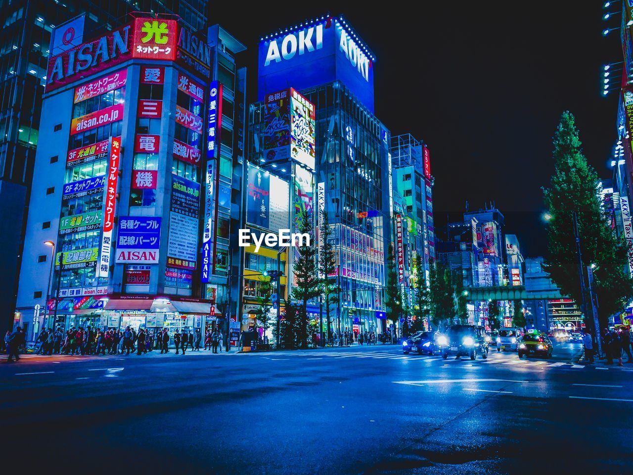 illuminated, city, building exterior, night, built structure, architecture, street, building, transportation, city life, city street, road, advertisement, office building exterior, crowd, car, sign, communication, motor vehicle, tall - high, outdoors, modern, skyscraper, cityscape, nightlife, financial district