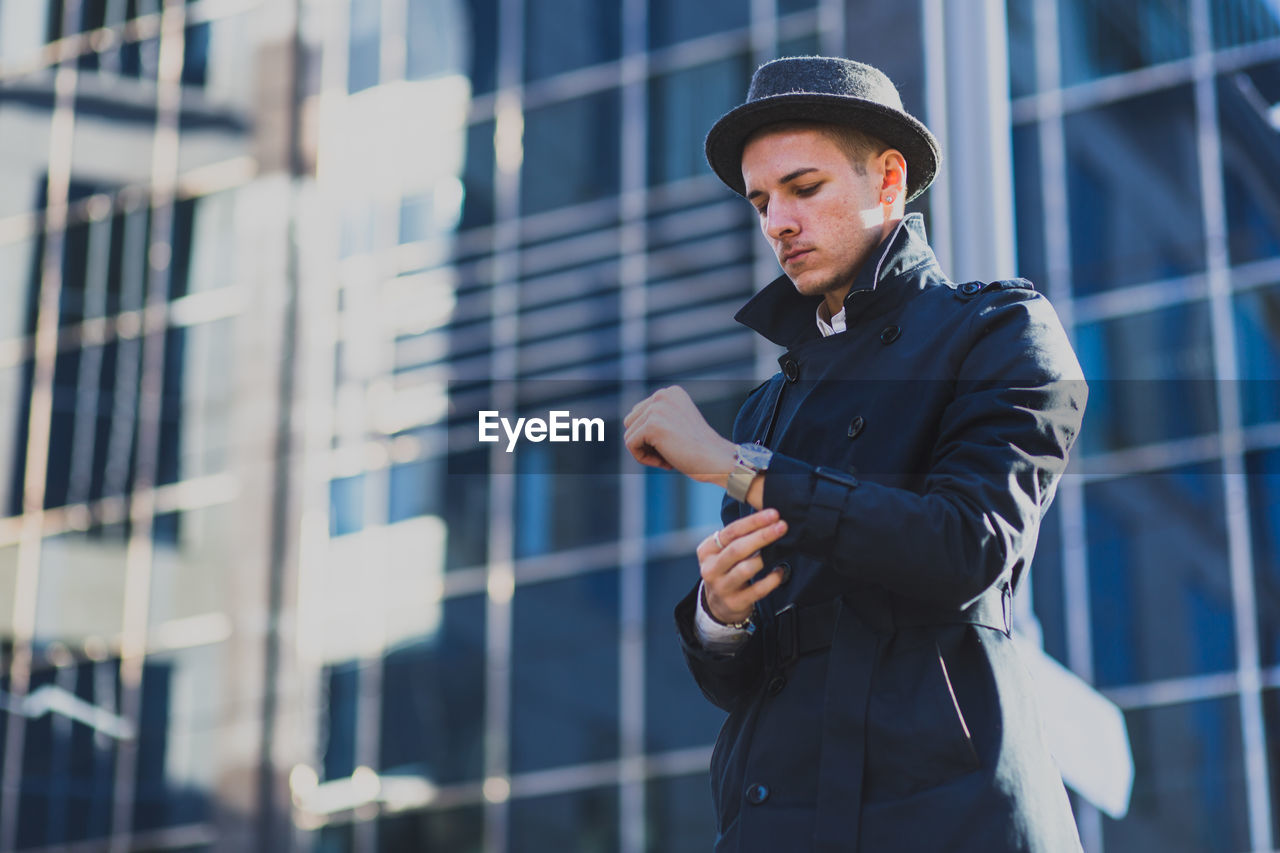 Man In Coat And Hat Standing In City
