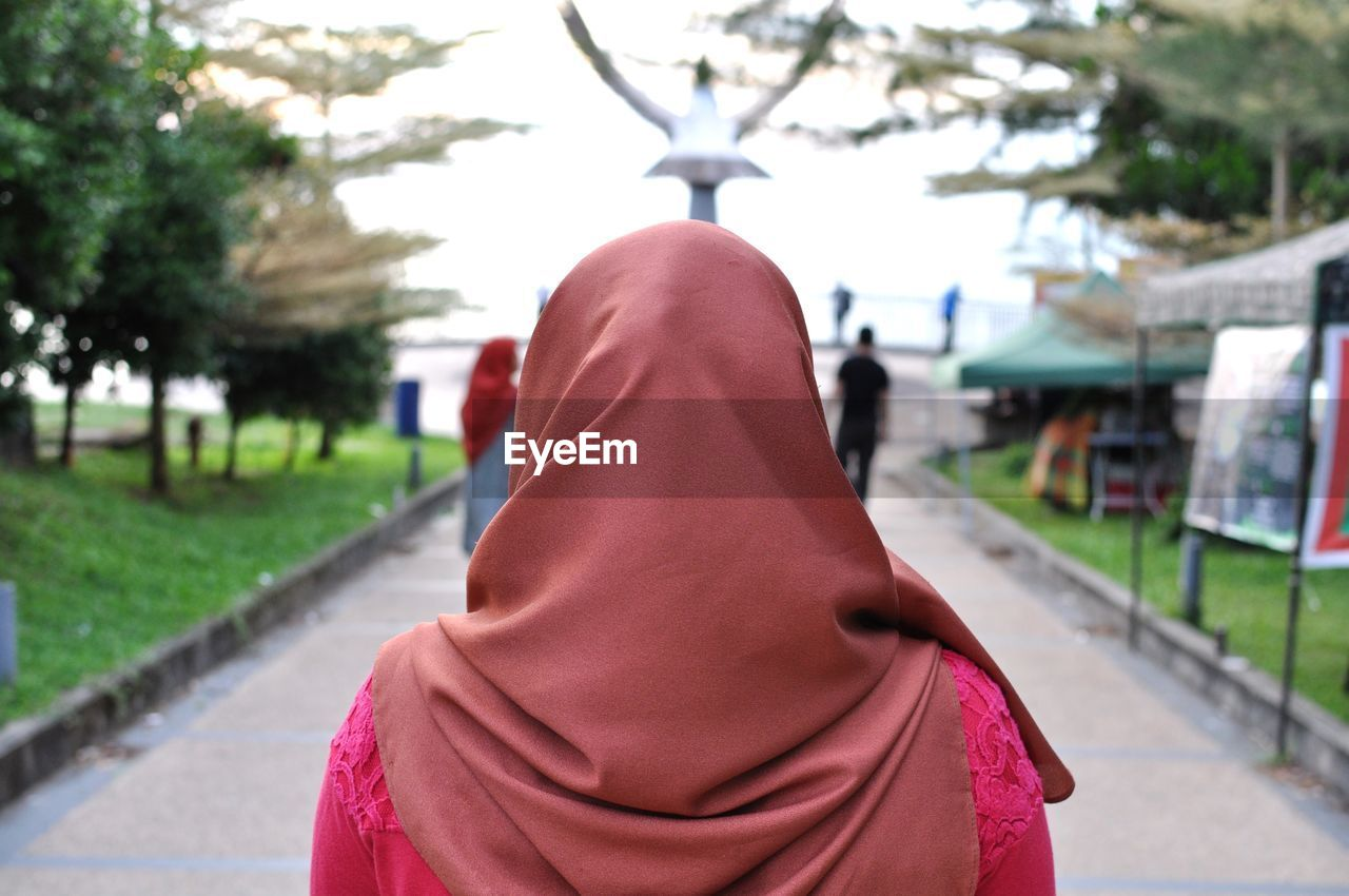 clothing, one person, focus on foreground, rear view, real people, day, lifestyles, women, architecture, standing, adult, pink color, hijab, hood, leisure activity, walking, city, portrait, footpath, outdoors, hood - clothing