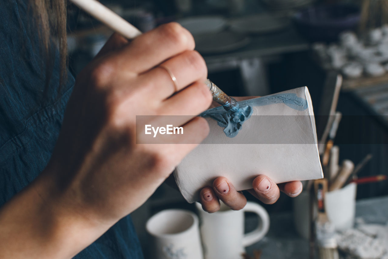 Close-Up Of Woman Painting Pottery