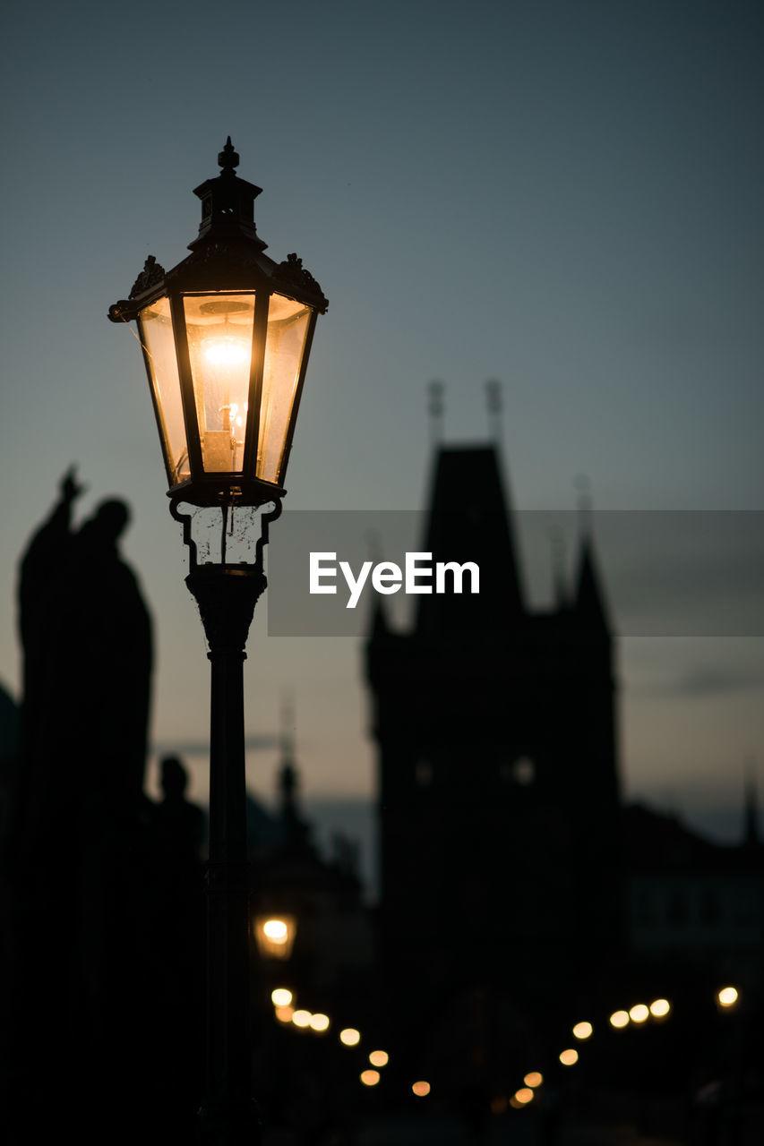 Illuminated gas light by historic building against sky at dusk
