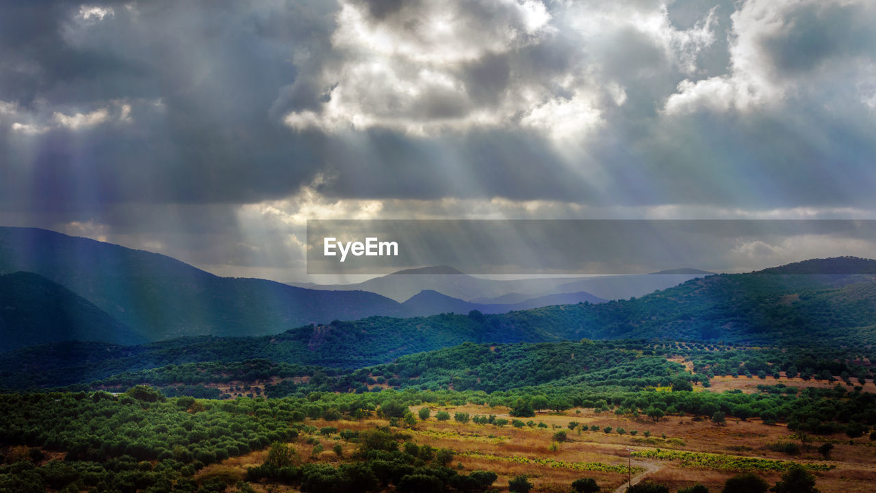 Sunlight streaming through clouds on landscape
