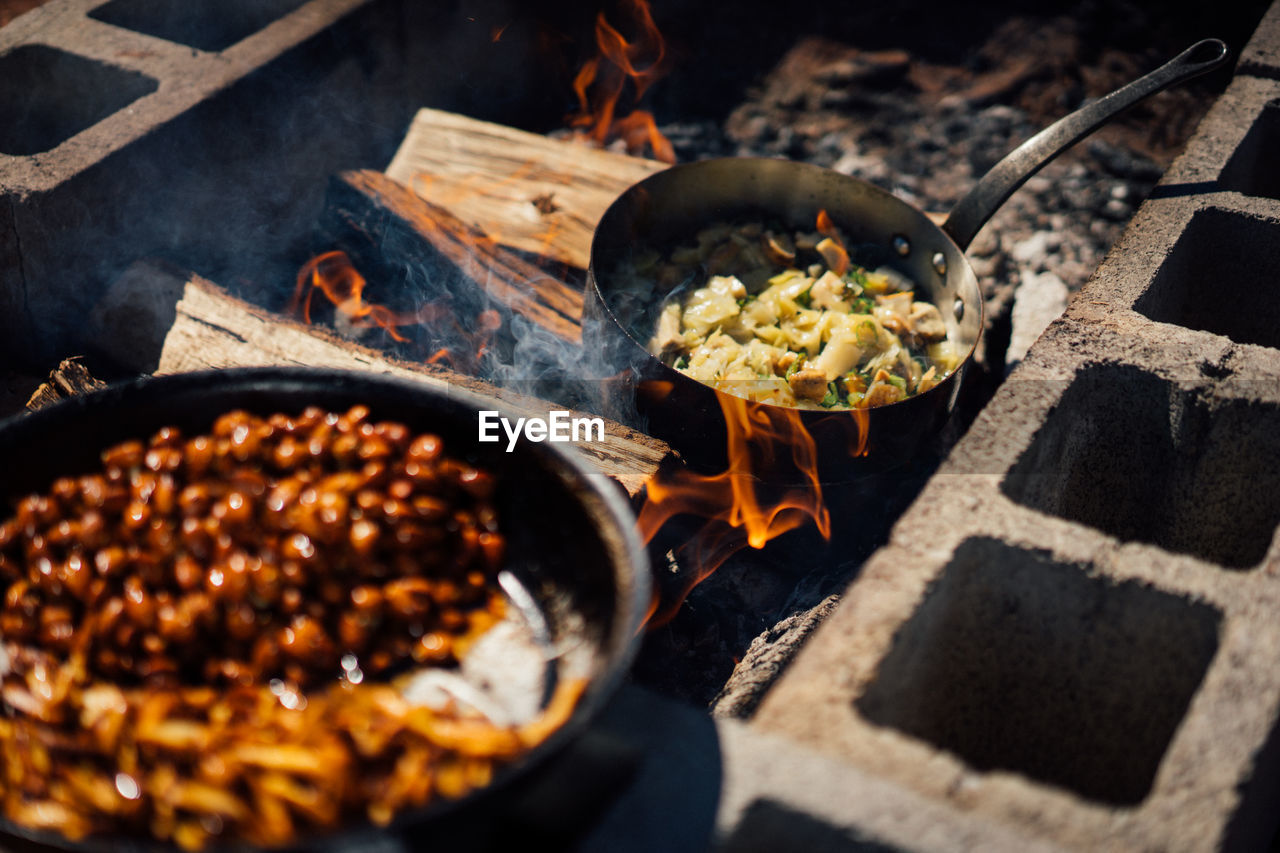 food and drink, food, heat - temperature, preparation, freshness, burning, kitchen utensil, fire, flame, no people, high angle view, fire - natural phenomenon, pan, cooking pan, household equipment, nature, healthy eating, wellbeing, sunlight, meat, preparing food, frying pan, skillet- cooking pan