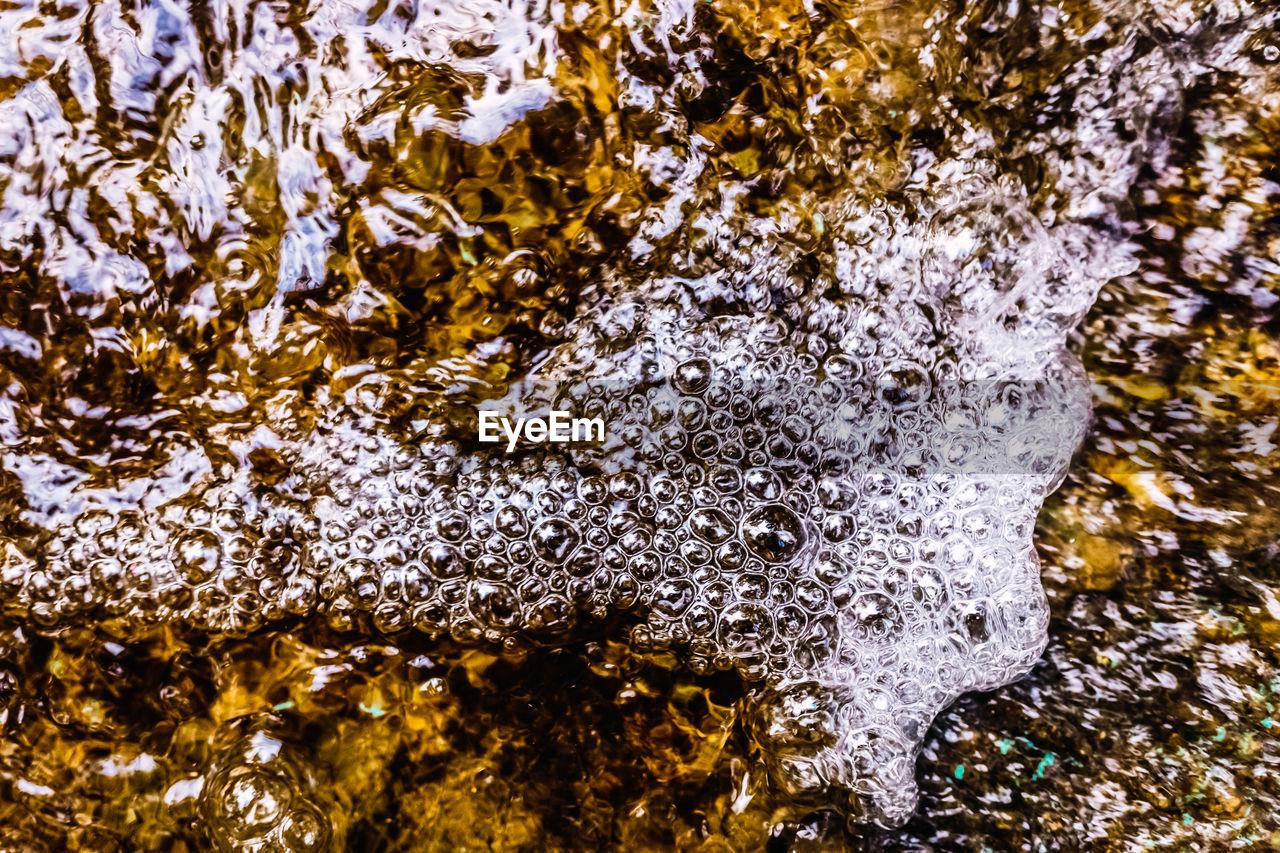 FULL FRAME SHOT OF WATER FLOWING THROUGH ROCKS IN WINTER