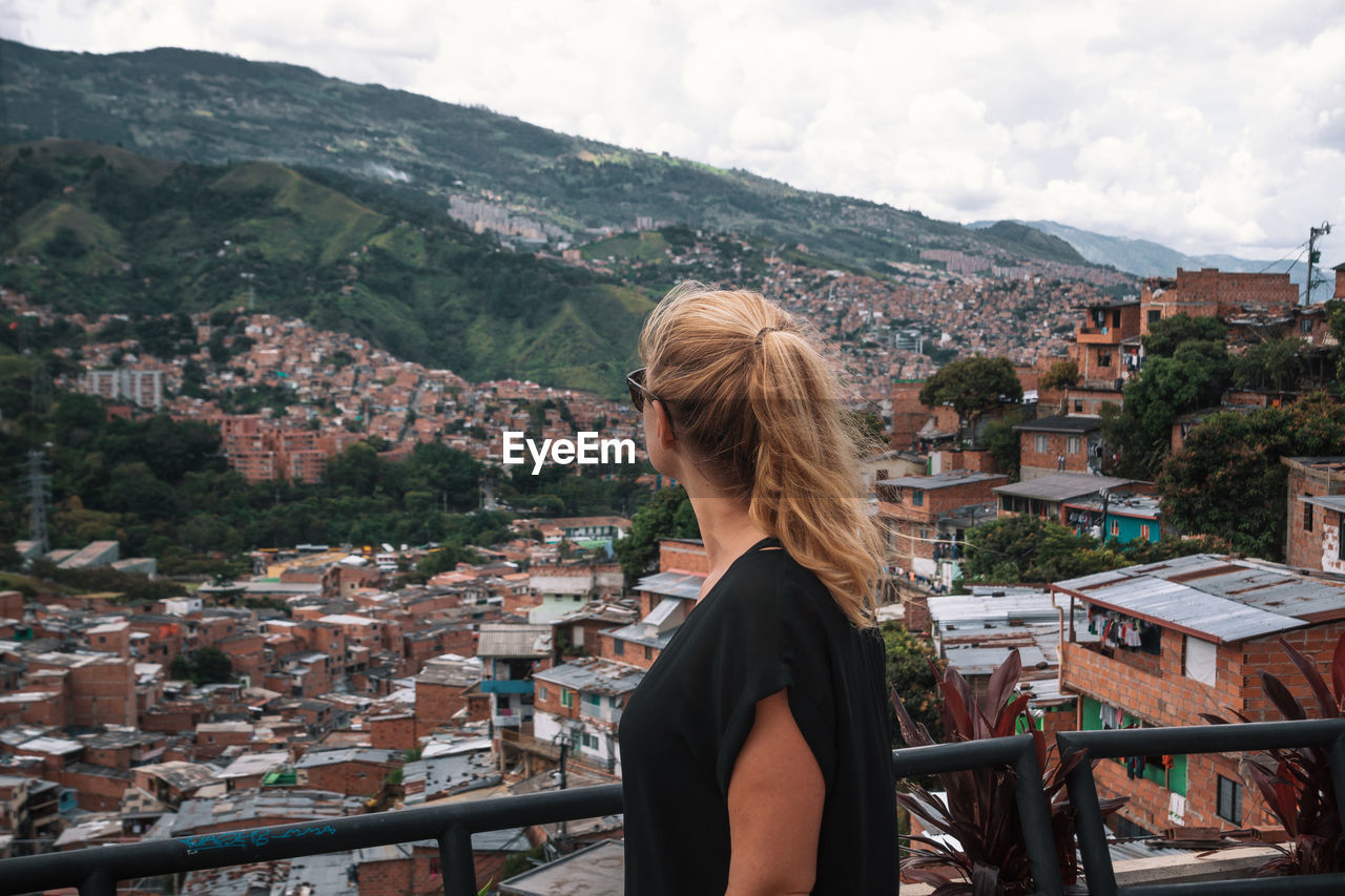 architecture, building exterior, built structure, one person, mountain, real people, lifestyles, hair, leisure activity, city, building, blond hair, nature, day, sky, women, adult, residential district, young adult, outdoors, hairstyle, looking at view, cityscape, townscape