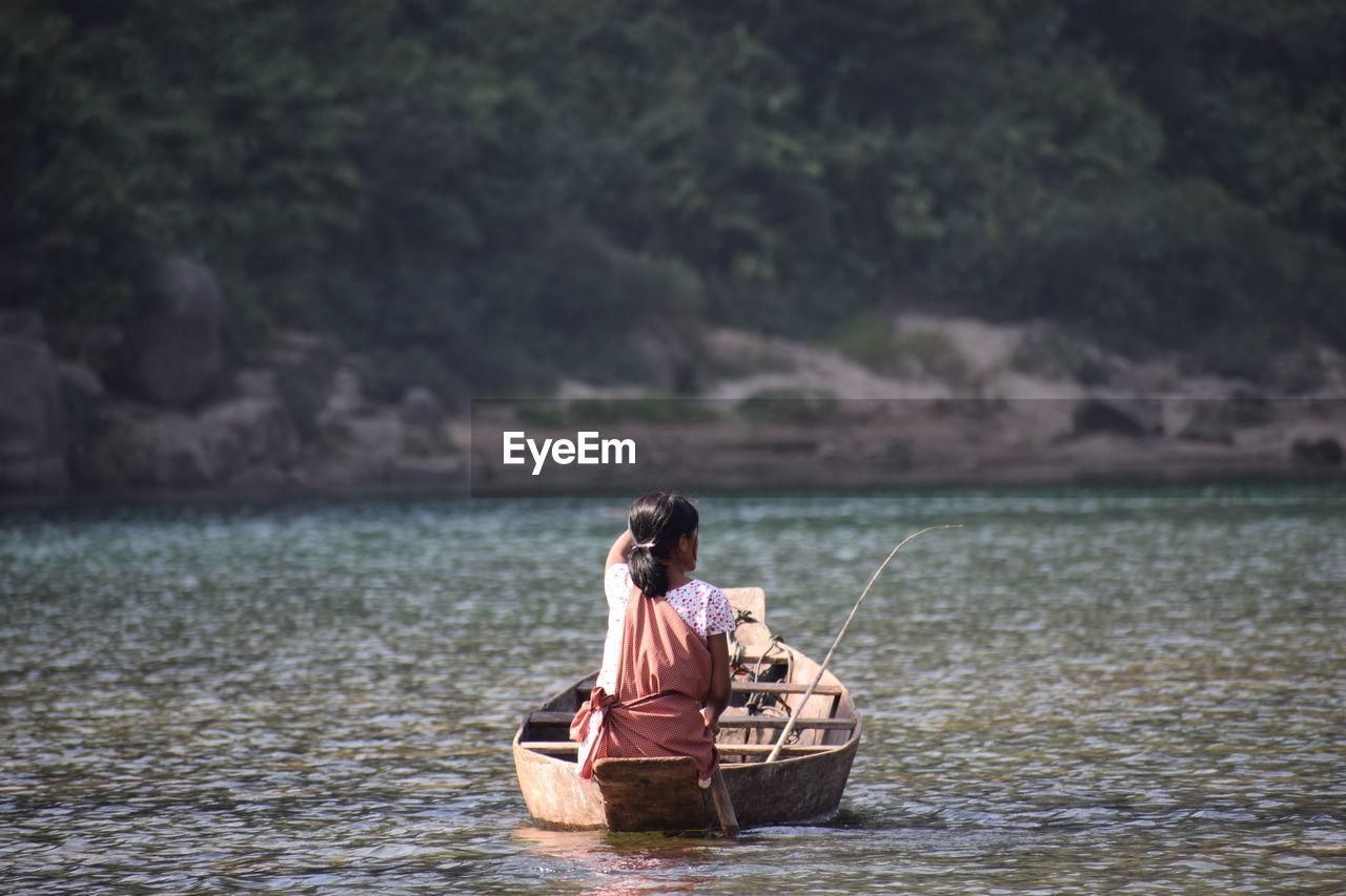 Rear view of woman fishing in lake
