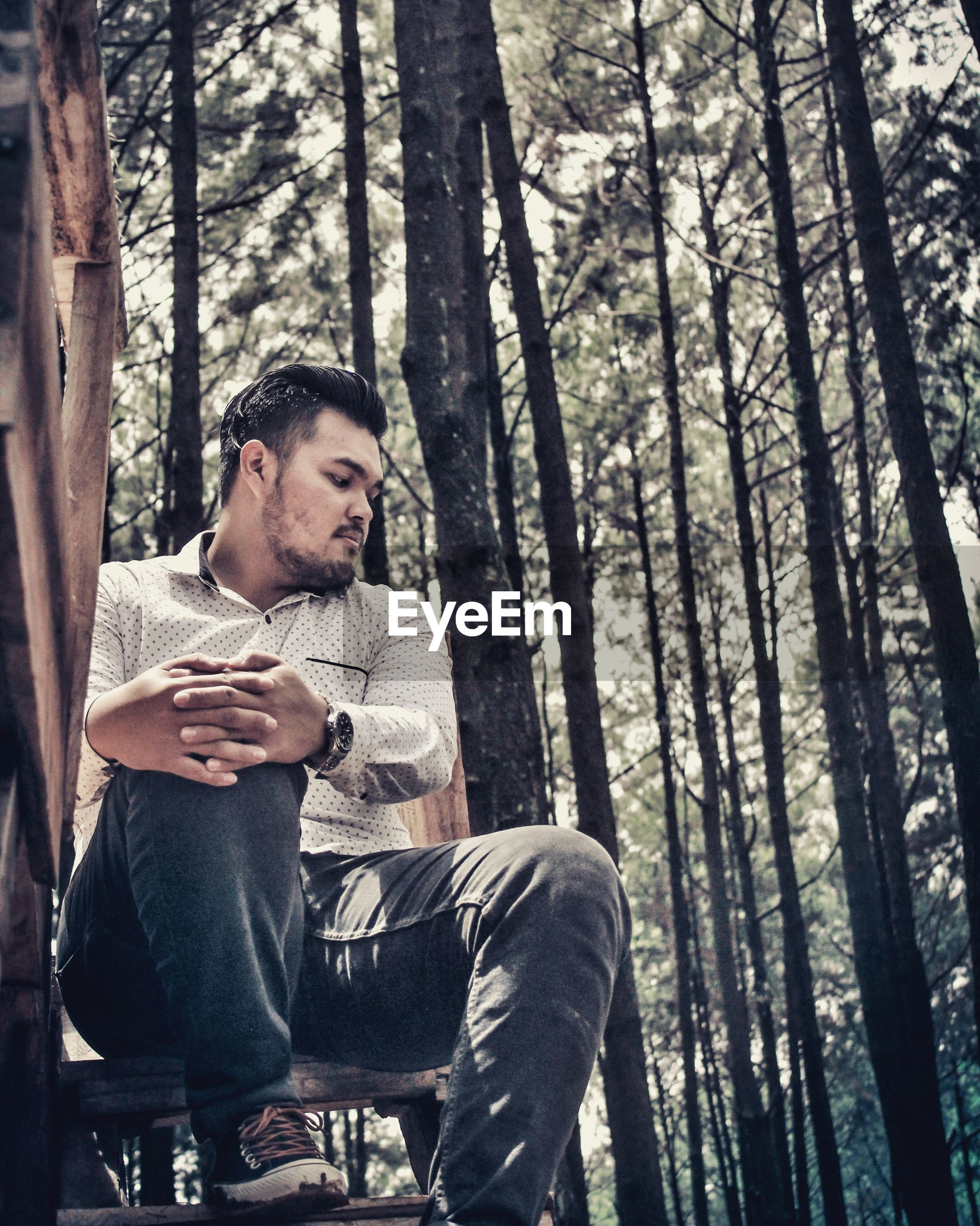 Young man looking down while sitting on tree trunk