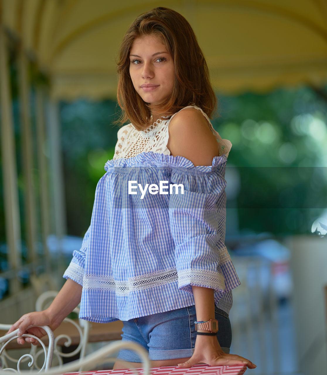 Portrait of teenage girl standing in cafe