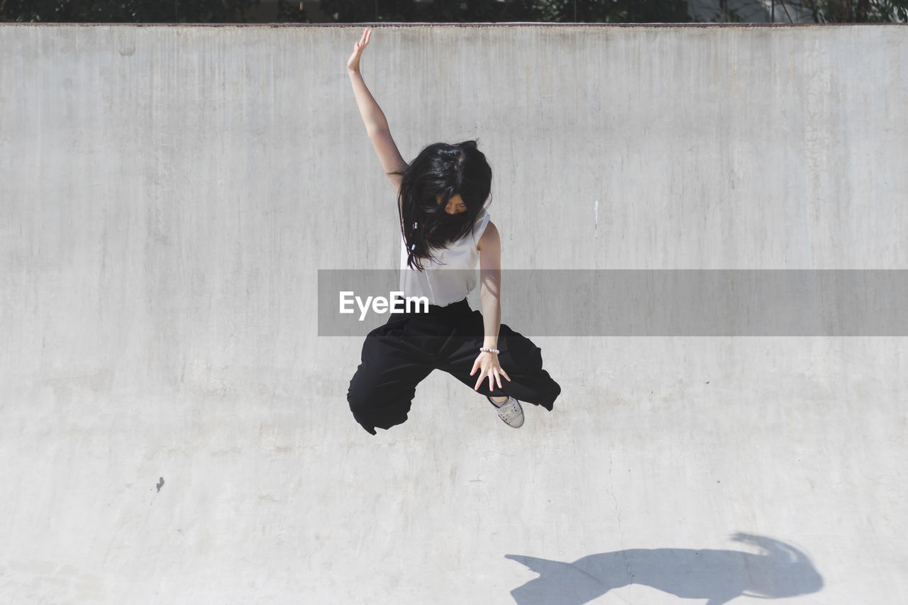 Full Length Of Young Woman Jumping Outdoors