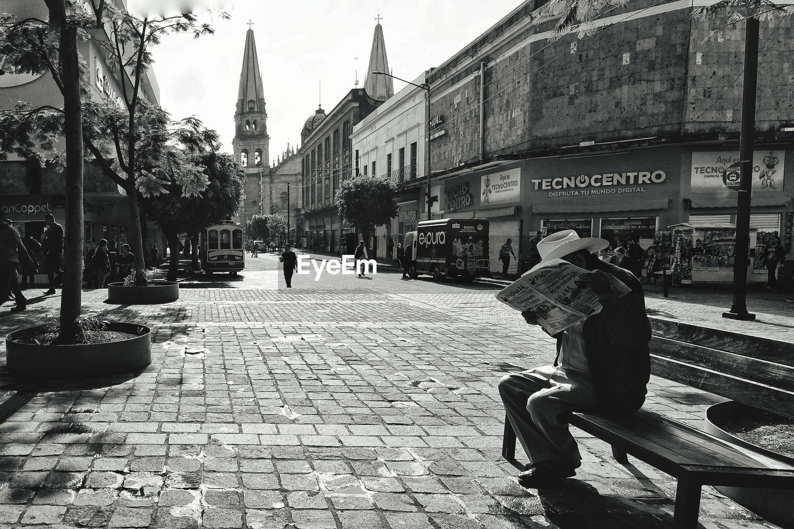 PEOPLE SITTING ON FOOTPATH BY BUILDINGS