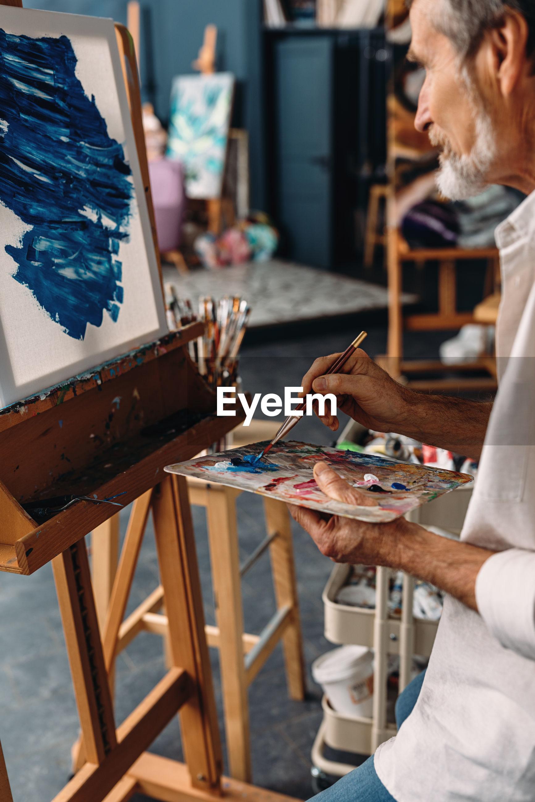 Senior man painting on easel