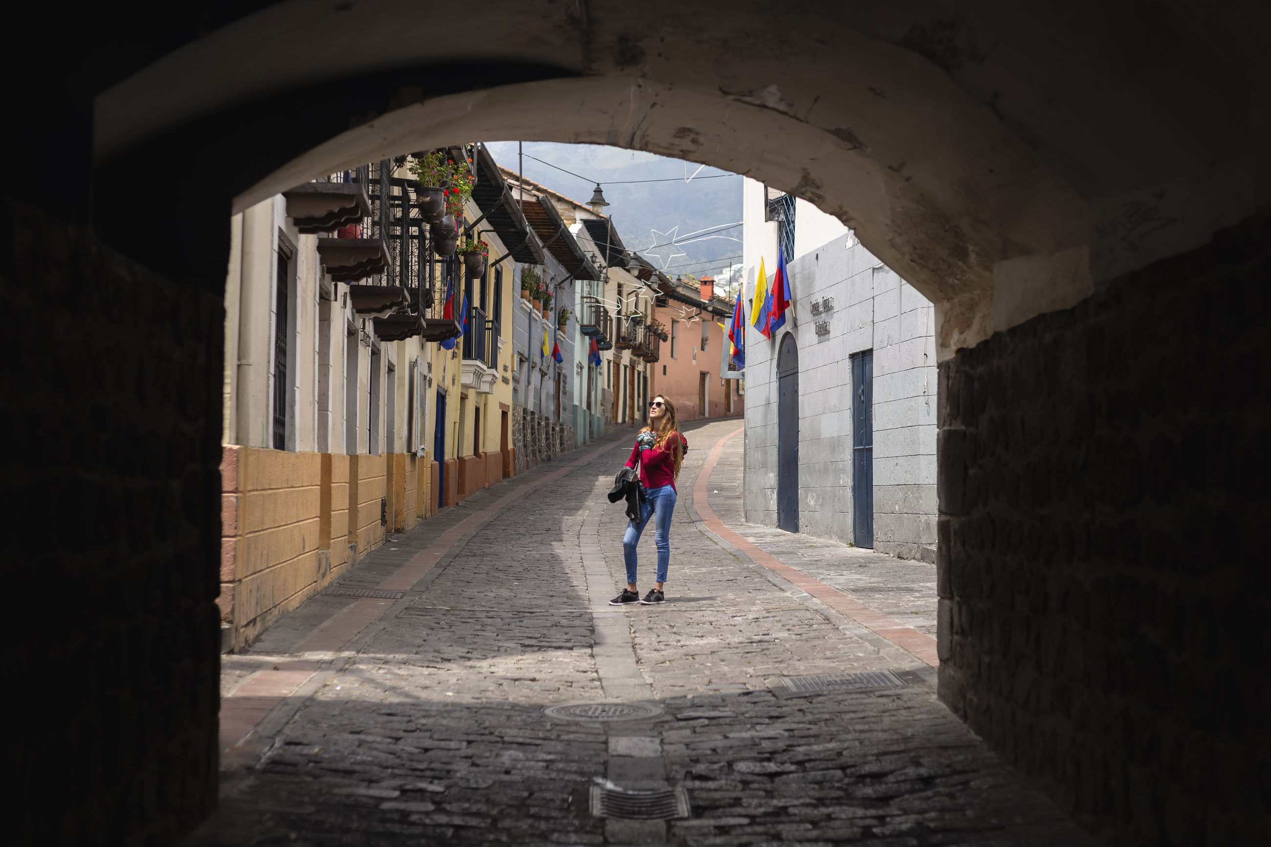 Woman standing in alley amidst buildings