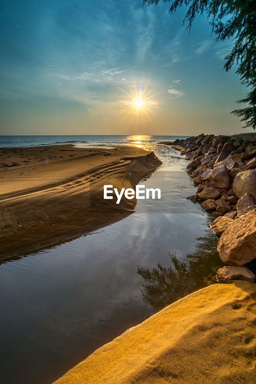 water, sky, beauty in nature, scenics - nature, sea, tranquility, tranquil scene, land, beach, sunset, nature, sun, non-urban scene, cloud - sky, reflection, sunlight, idyllic, no people, horizon, horizon over water, outdoors, bright