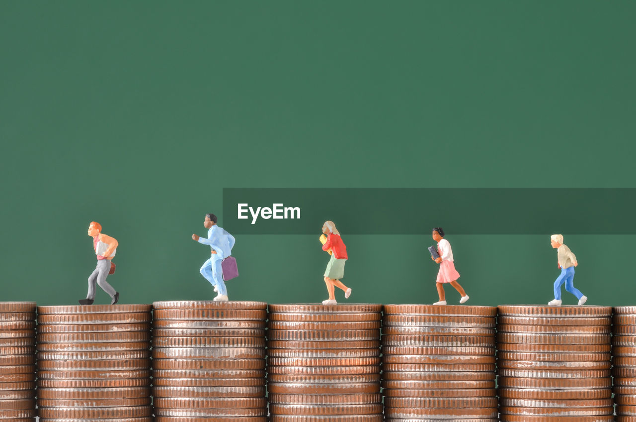 Close-up of figurines on stacked coins against green wall