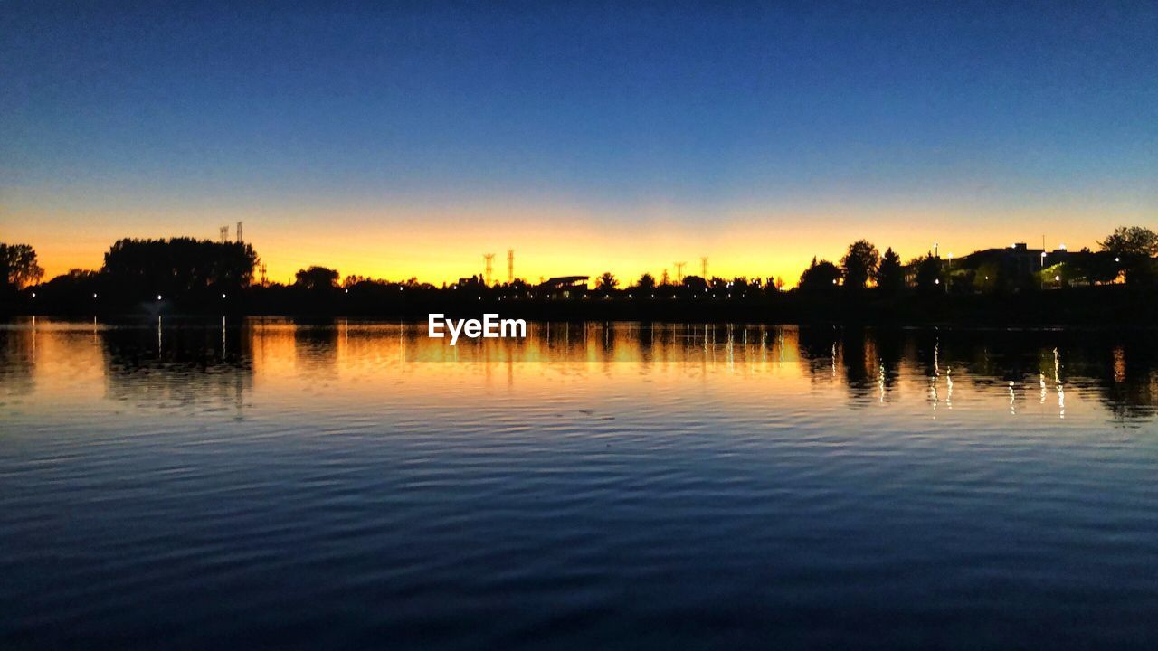 water, sky, reflection, tranquility, lake, tranquil scene, tree, waterfront, scenics - nature, beauty in nature, nature, no people, clear sky, copy space, sunset, plant, silhouette, blue, outdoors