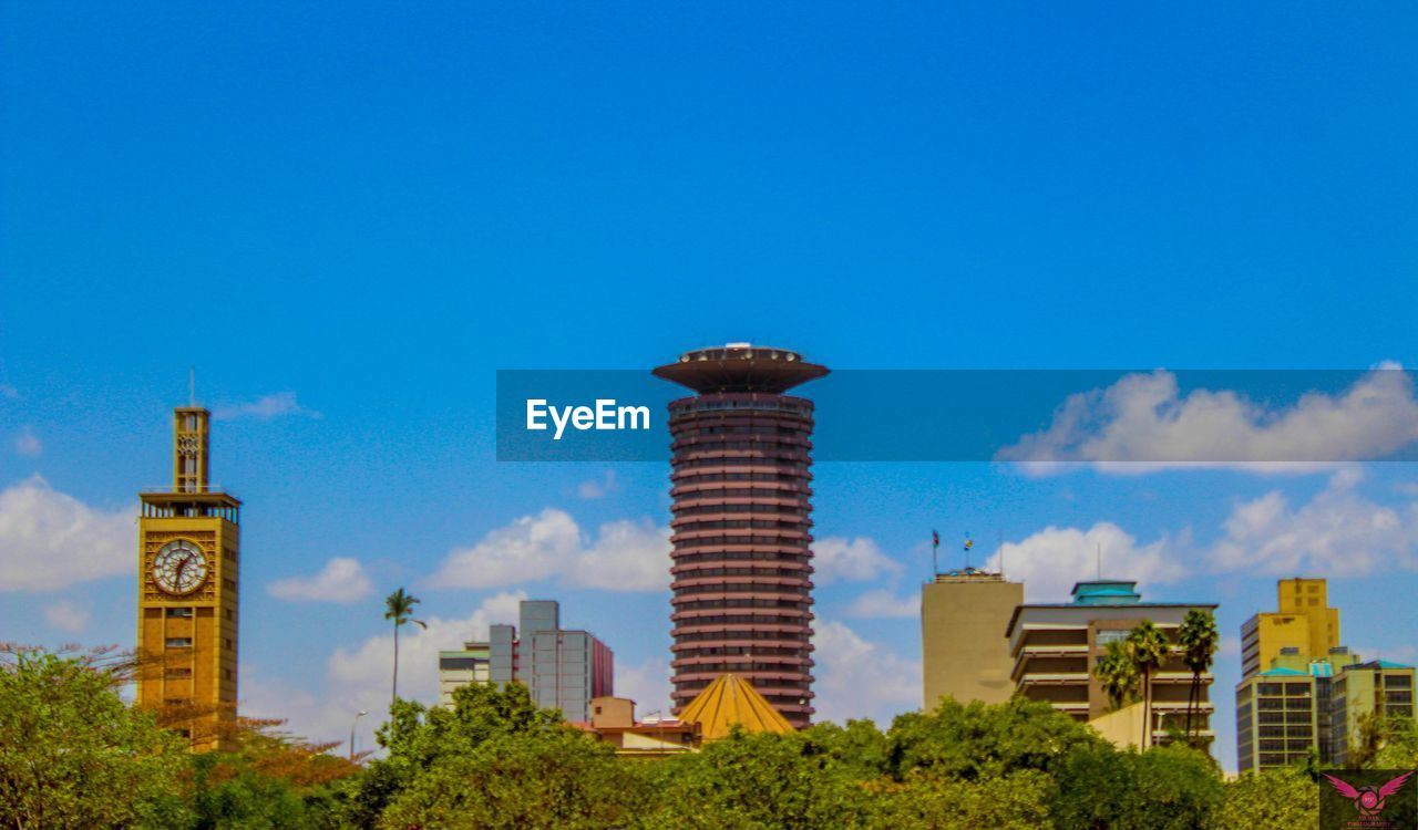 sky, building exterior, built structure, architecture, blue, nature, building, day, plant, copy space, no people, city, tower, cloud - sky, tree, outdoors, office building exterior, low angle view, skyscraper, tall - high
