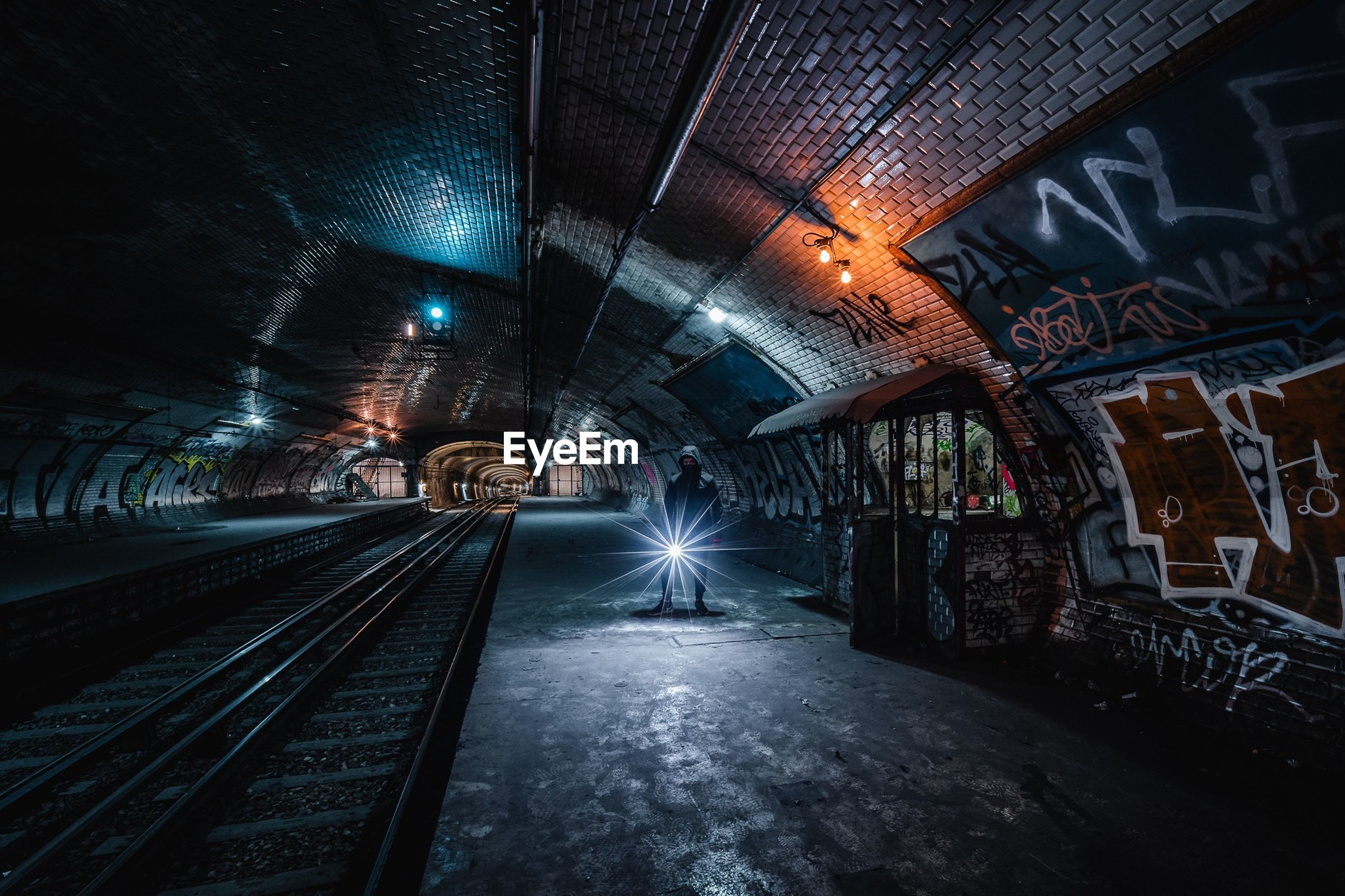 illuminated, architecture, transportation, tunnel, built structure, diminishing perspective, indoors, no people, the way forward, direction, lighting equipment, track, rail transportation, mode of transportation, public transportation, railroad track, graffiti, vanishing point, night, subway, ceiling, light at the end of the tunnel, long