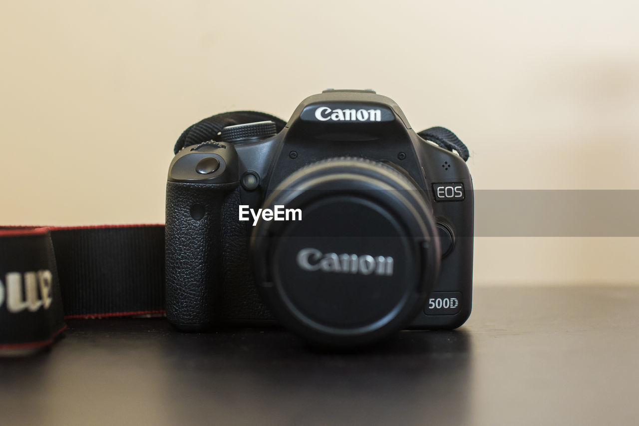 technology, photography themes, camera - photographic equipment, photographic equipment, camera, digital camera, black color, text, close-up, indoors, still life, lens - optical instrument, no people, number, table, modern, western script, equipment, communication, retro styled, digital single-lens reflex camera, slr camera, personal accessory