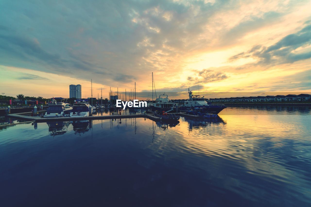 water, nautical vessel, sky, sunset, cloud - sky, reflection, transportation, mode of transport, built structure, harbor, waterfront, architecture, sea, travel destinations, nature, outdoors, building exterior, moored, beauty in nature, no people, scenics, commercial dock, yacht, city, day