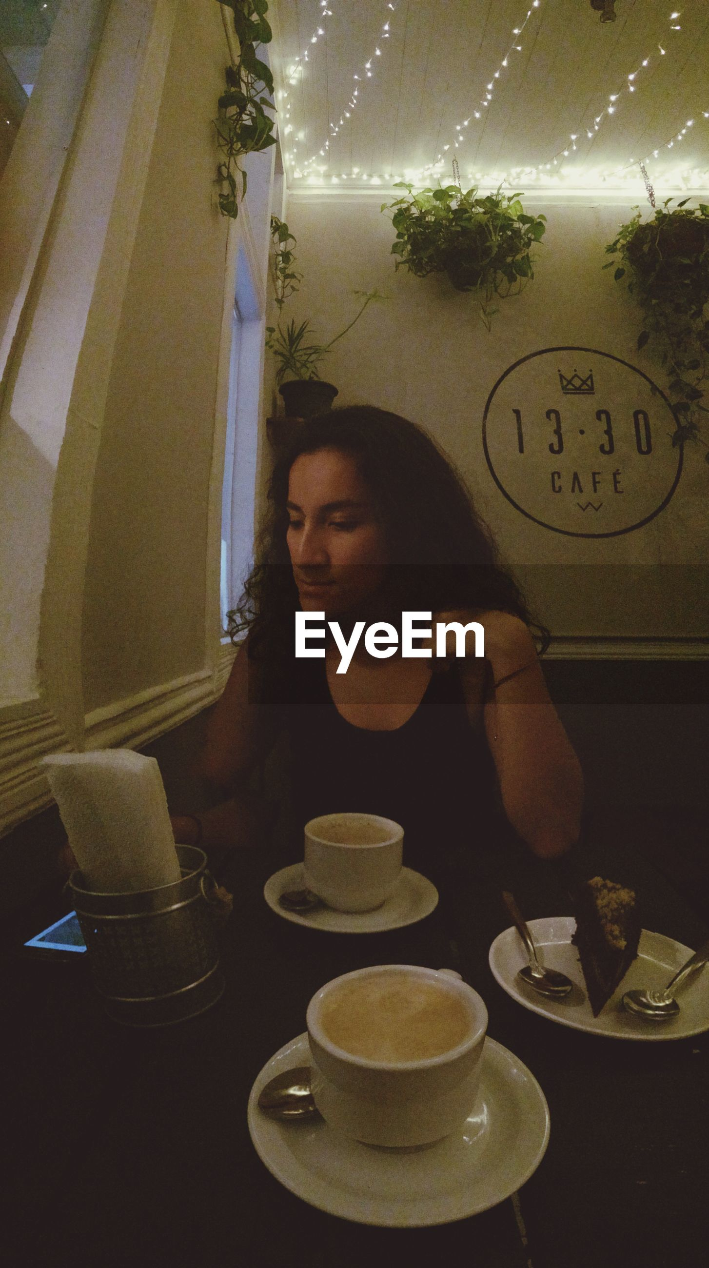 indoors, lifestyles, leisure activity, person, young adult, food and drink, communication, drink, casual clothing, table, holding, front view, sitting, headshot, young women, looking at camera, restaurant, portrait
