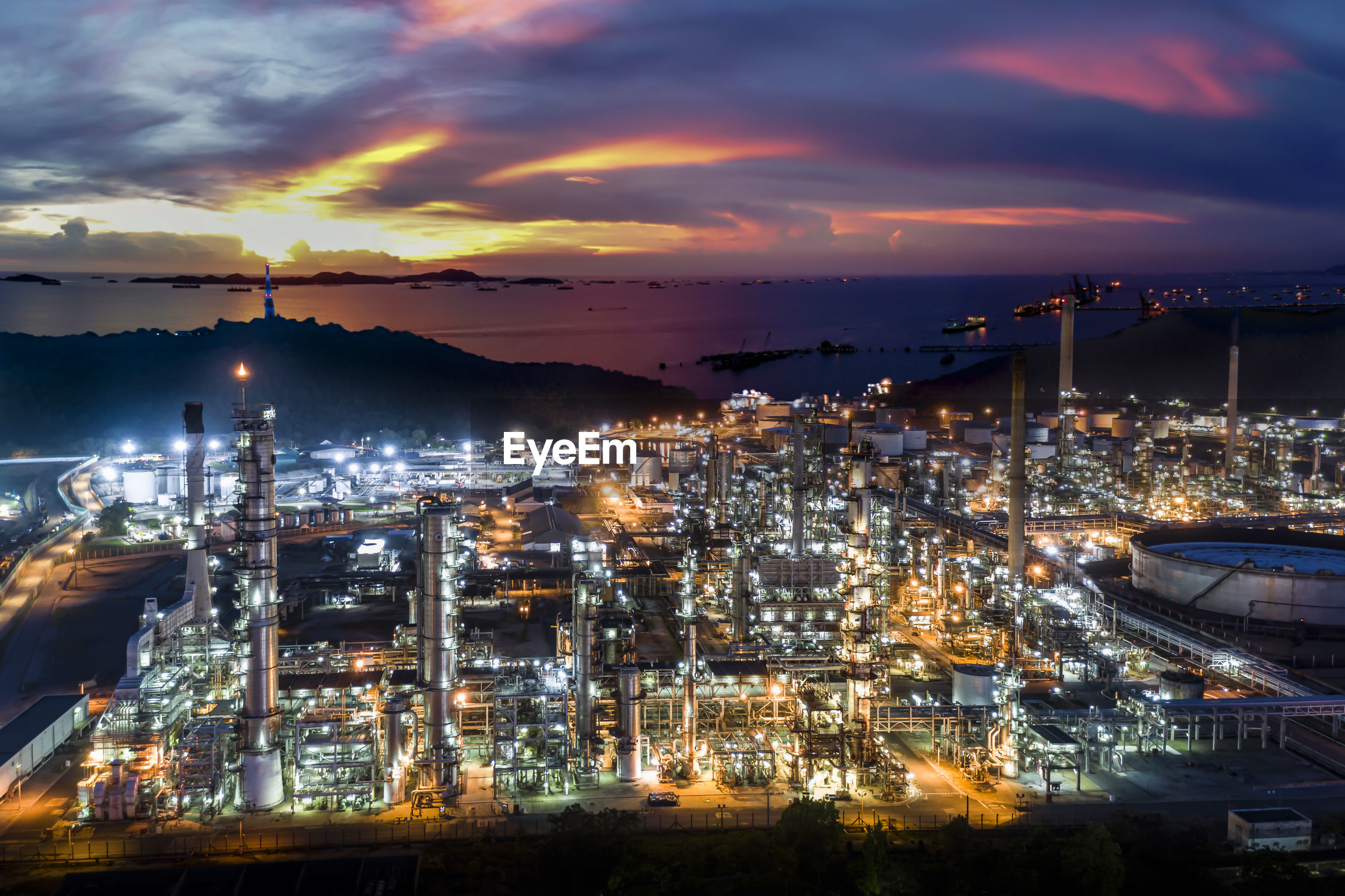 Oil refinery and petroleum industry factory zone at night over lighting with the sea