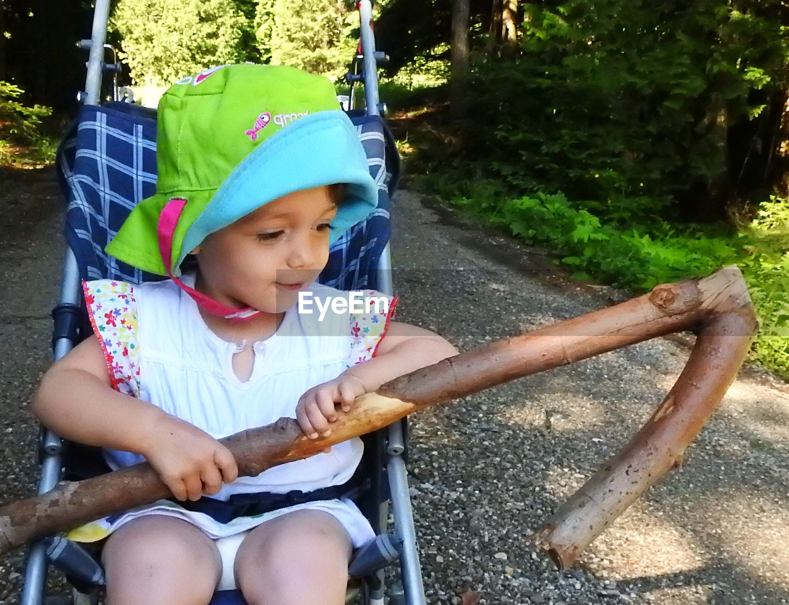 Close-up of girl holding stick while sitting on baby stroller at park