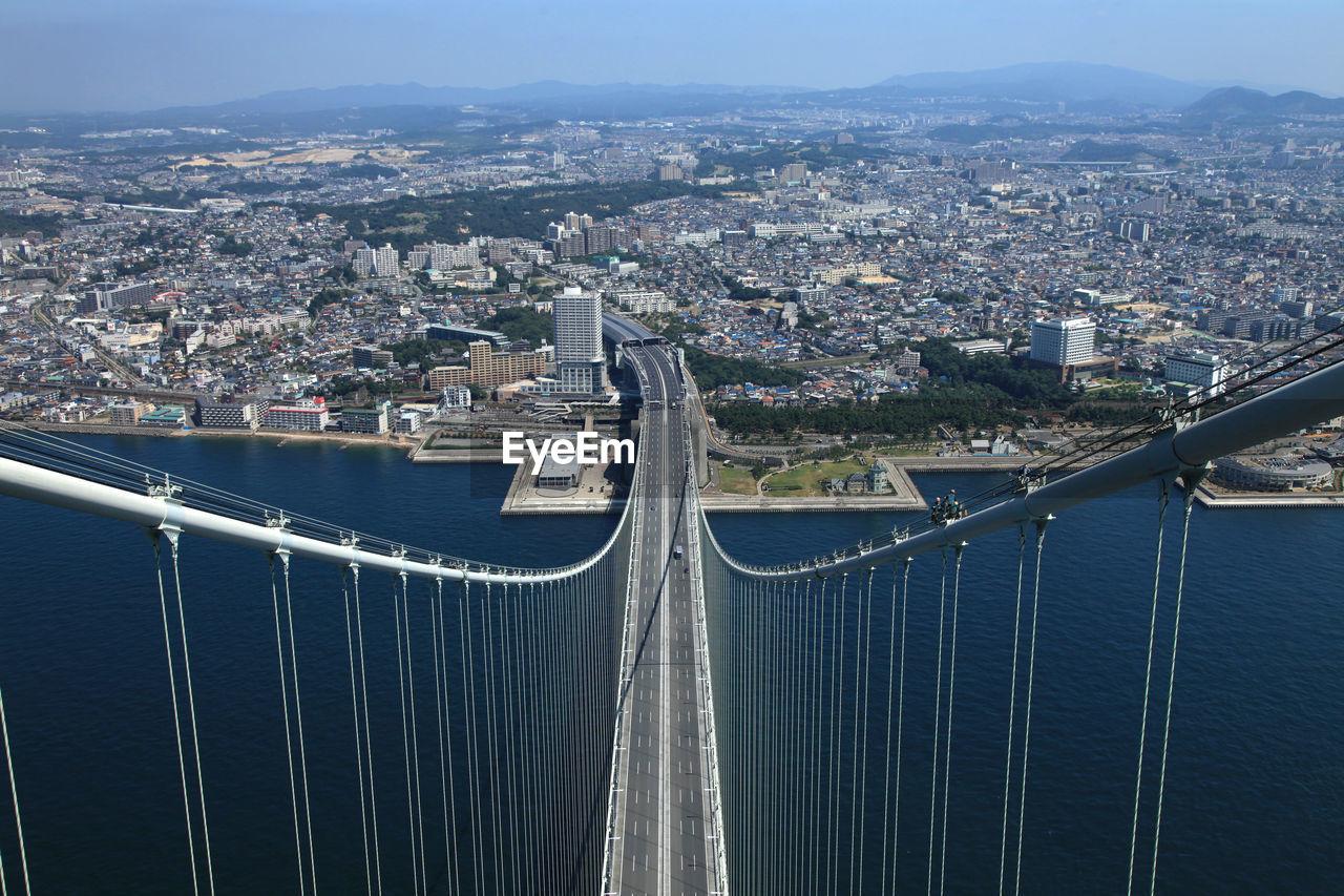 High Angle View Of Suspension Bridge Over Sea By Cityscape