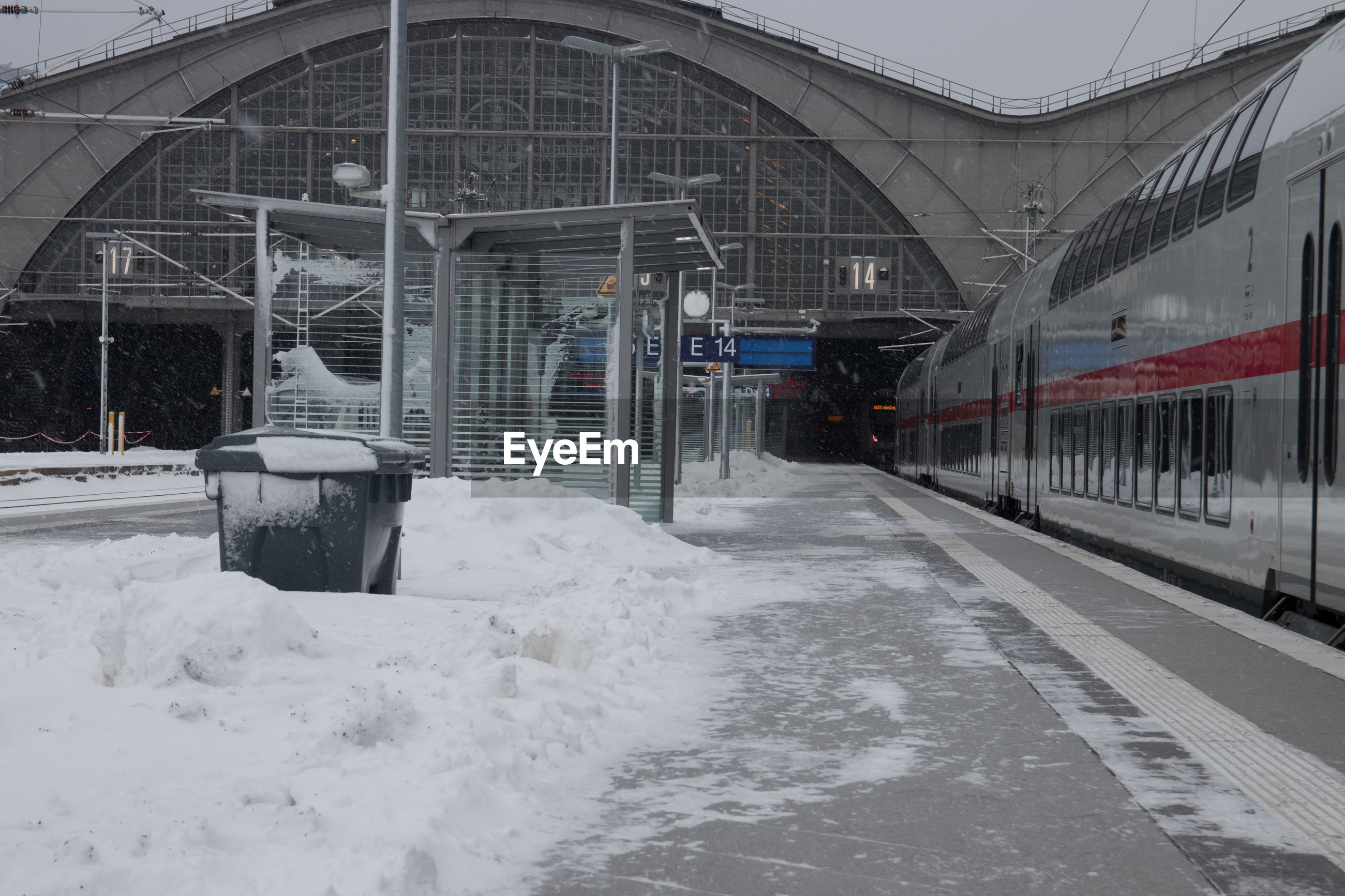 SNOW COVERED RAILROAD TRACKS AMIDST BUILDINGS