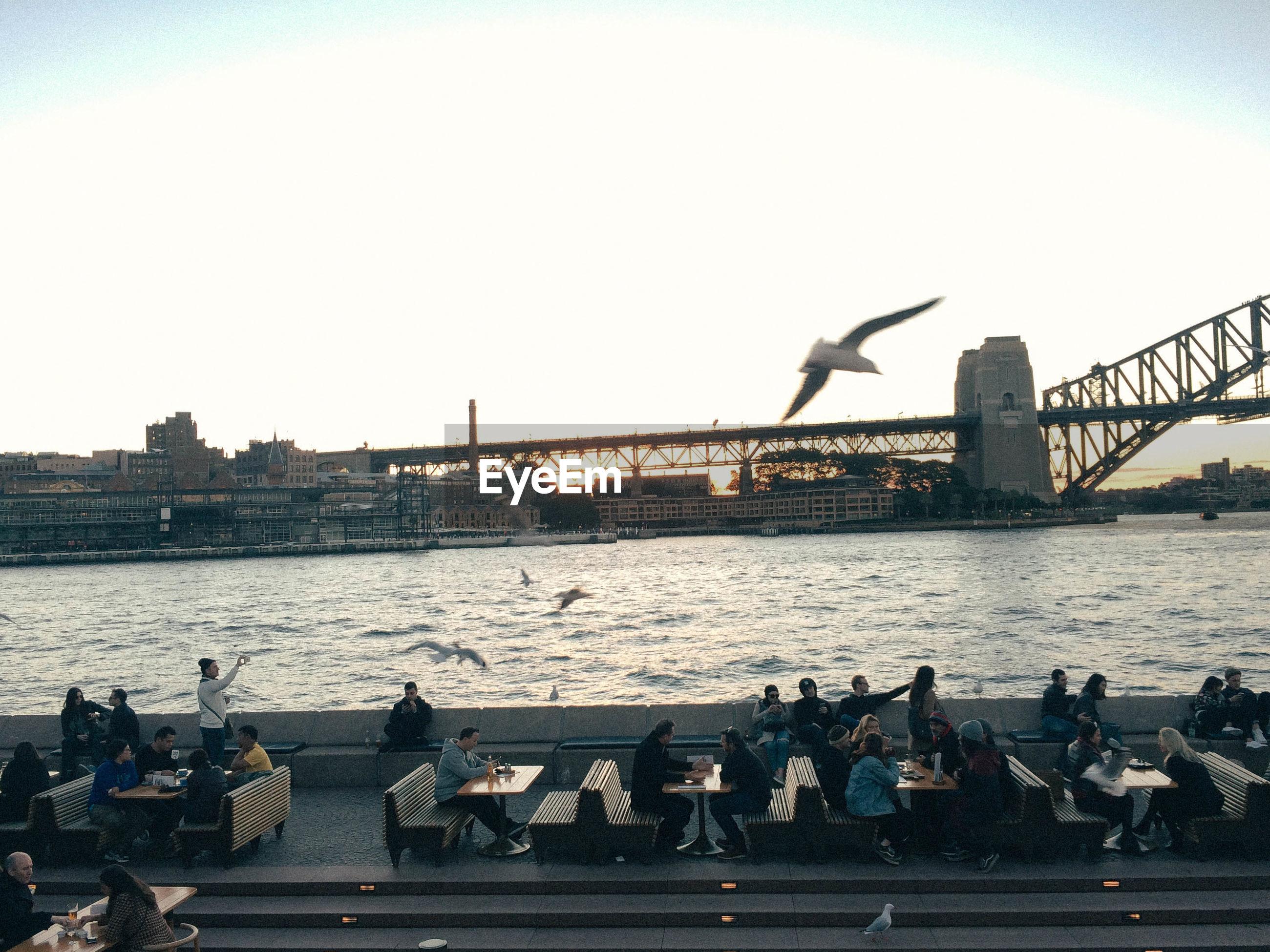 People at restaurant by river against sydney harbor bridge
