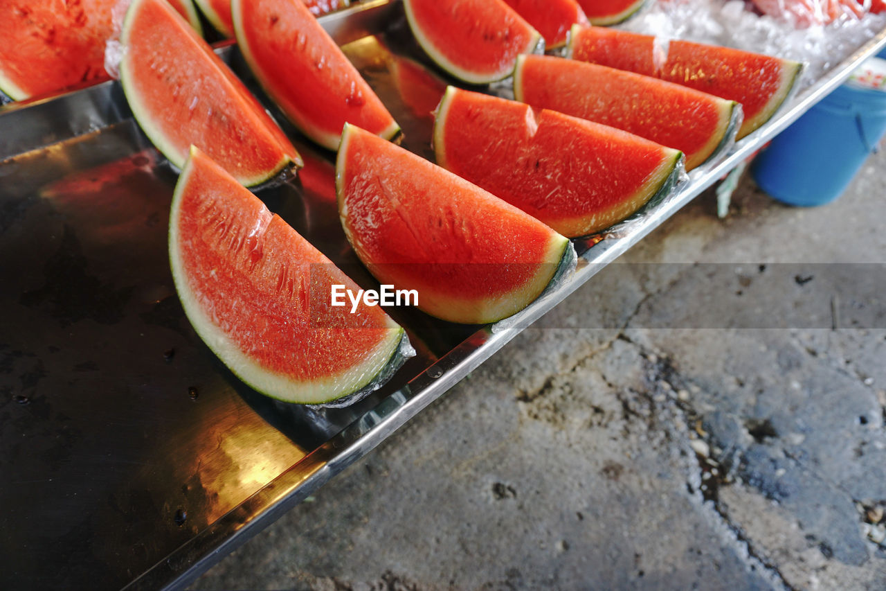 food and drink, food, freshness, fruit, healthy eating, wellbeing, still life, slice, high angle view, no people, close-up, red, indoors, day, watermelon, table, orange color, preparation, focus on foreground, ripe, tray