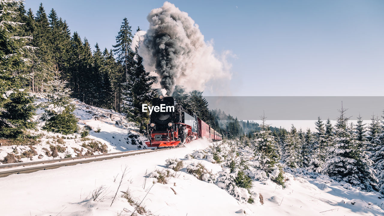 snow, winter, cold temperature, plant, tree, transportation, mode of transportation, nature, sky, day, train, rail transportation, smoke - physical structure, beauty in nature, train - vehicle, steam train, white color, mountain, covering, no people, outdoors, snowcapped mountain, track, pollution