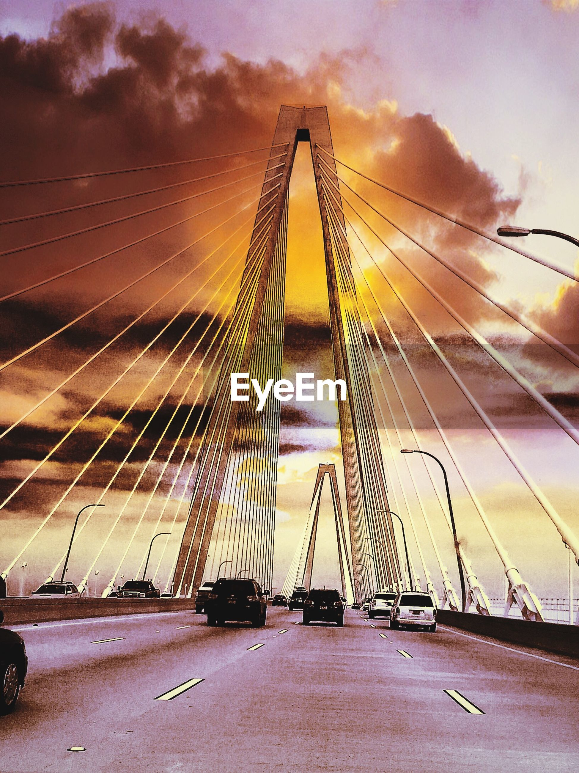 sky, transportation, cloud - sky, the way forward, sunset, connection, engineering, cloudy, bridge - man made structure, suspension bridge, built structure, cloud, diminishing perspective, architecture, low angle view, outdoors, dusk, vanishing point, road, cable-stayed bridge
